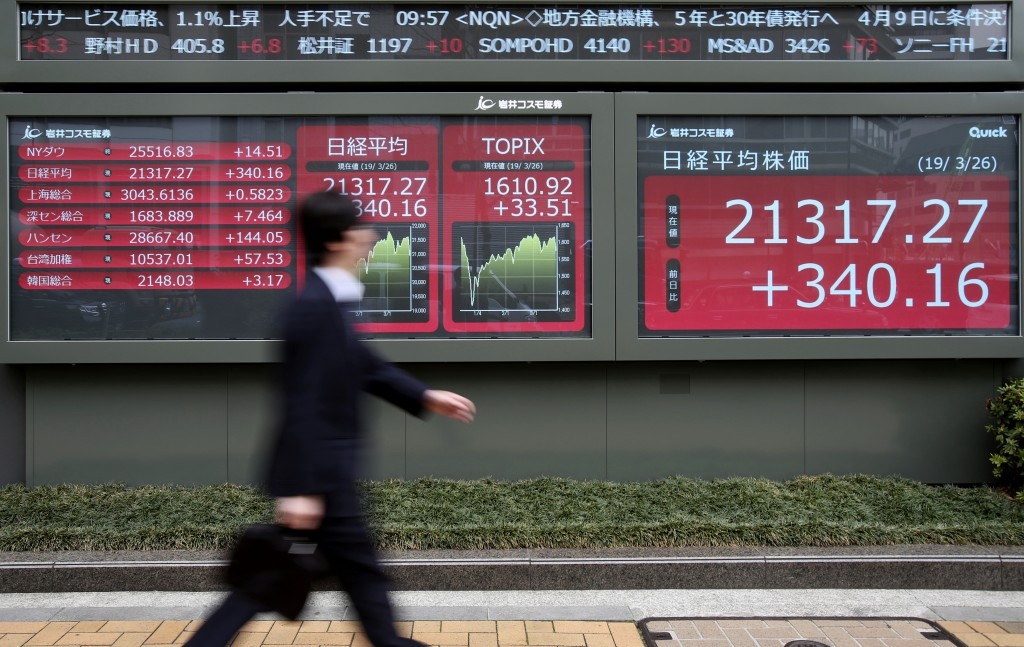 A man walks by an electronic stock board of a securities firm in Tokyo, Tuesday, March 26, 2019. Asian stock prices rebounded Tuesday after global mar