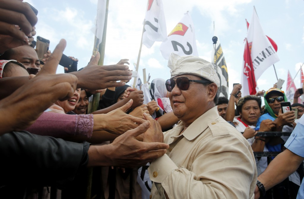 FILE - In this Tuesday, March 26, 2019, file photo, Indonesian presidential candidate Prabowo Subianto, center, greets his supporters during a rally i