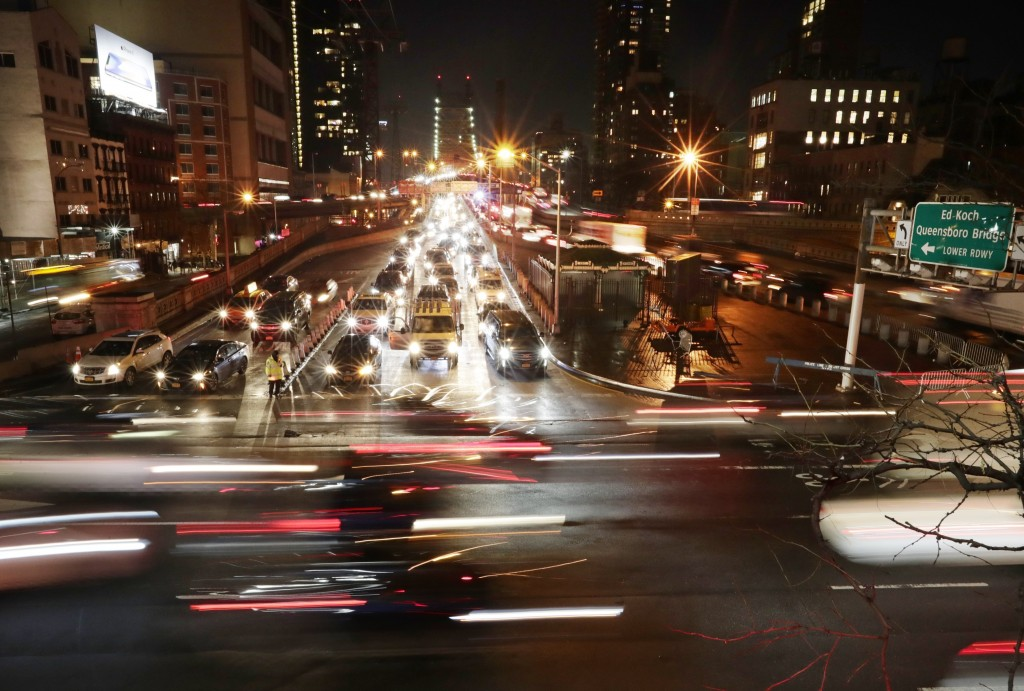 FILE- In this Jan. 11, 2018, file photo, cars pass the Queensboro Bridge in New York. Ride-hailing giants Uber and Lyft have redefined what we expect ...