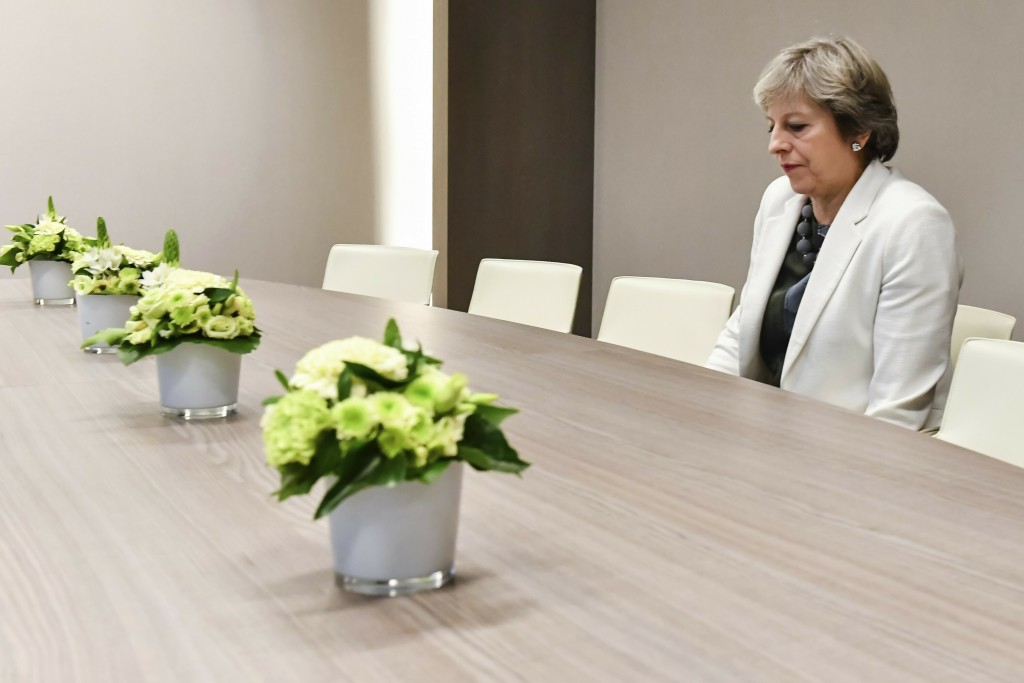 FILE - In this Friday, Oct. 20, 2017 file photo, British Prime Minister Theresa May waits for the arrival of European Council President Donald Tusk pr