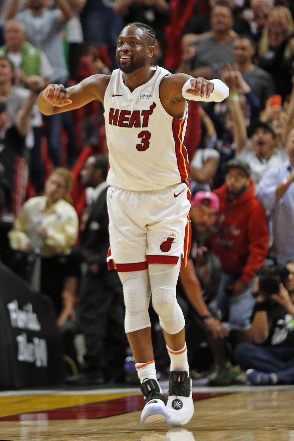 Miami Heat guard Dwyane Wade (3) runs up the court to celebrate the win against the Dallas Mavericks at an NBA basketball game, Thursday, March 28, 20