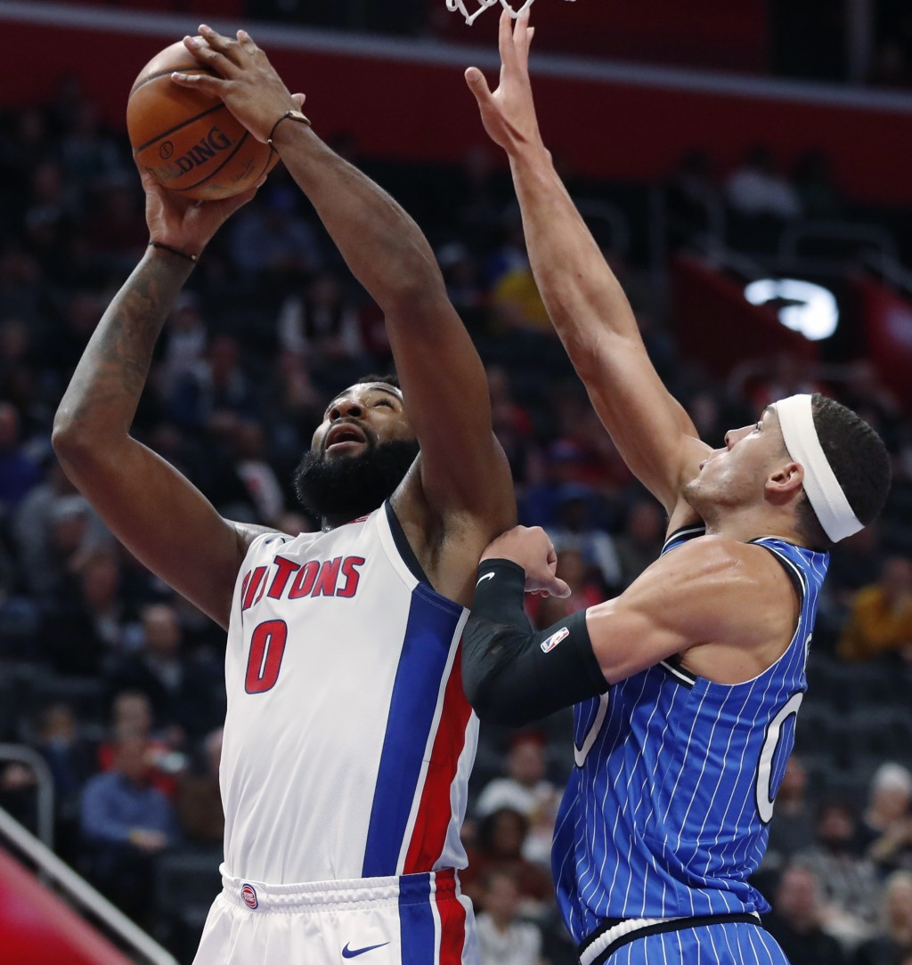Detroit Pistons center Andre Drummond, left, attempts a layup as Orlando Magic forward Aaron Gordon defends during the first half of an NBA basketball...