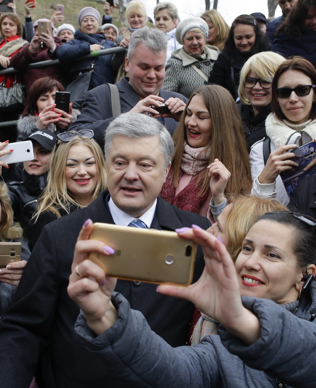 Ukrainian President Petro Poroshenko, center, poses for a selfie with a supporter after a public prayer ahead of Sunday's presidential election at the