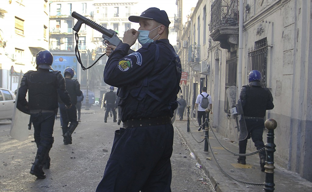 A police officers walks with a teargas rifle during clashes in Algiers, Algeria, March 29, 2019. Algerians taking to the streets for their sixth strai...