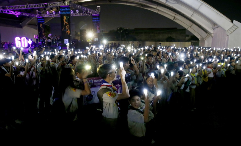Philippine Boy Scouts switch on their flashlights at the countdown for the 12th Earth Hour event Saturday, March 30, 2019 in suburban Makati city east...