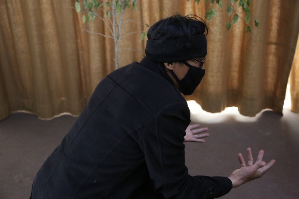 In this Feb. 26, 2019 photo, Abdullah, a former Afghan fighter in Syria with the Fatimiyoun Brigade, wears a mask to hid his identity during an interv...