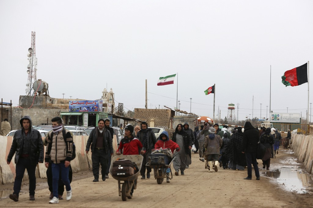 In This Wednesday, Feb. 20, 2019, photo, Afghans return to Afghanistan at the Islam Qala border with Iran, in the western Herat Province. Security off...