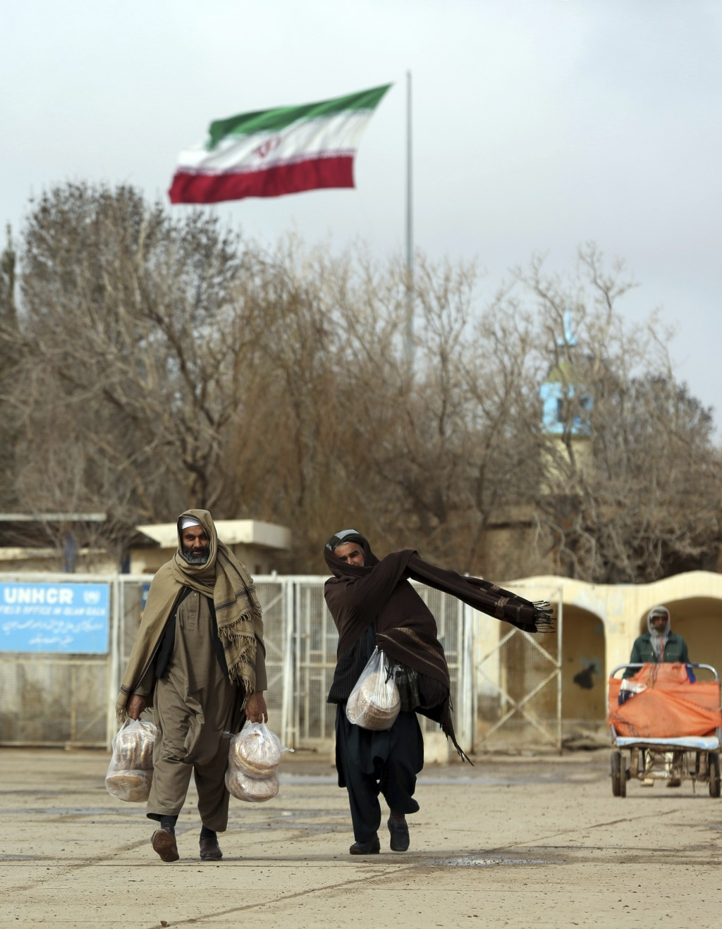 In this Feb. 20, 2019 photo, Afghans return to Afghanistan at the Islam Qala border with Iran, in the western Herat Province. Security officials worry