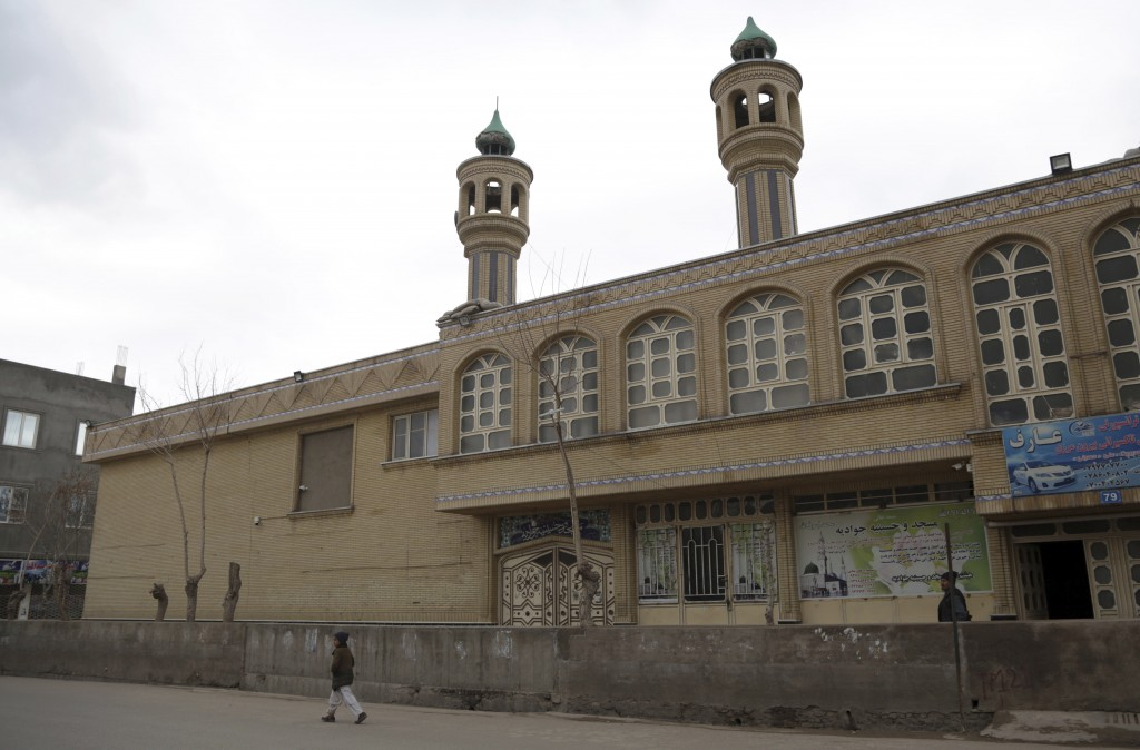 In this Feb. 20, 2019 photo, an Afghan boy walks past the Jawadia Shiite mosque that was targeted by by Islamic State gunmen last May, killing 38 peop...