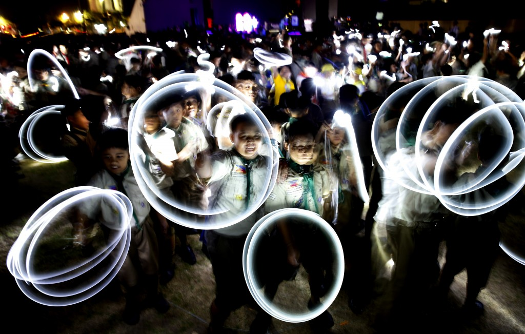 In this Saturday, March 30, 2019, file photo, Philippine Boy Scouts play with their flashlights at the countdown for the 12th Earth Hour event in subu...
