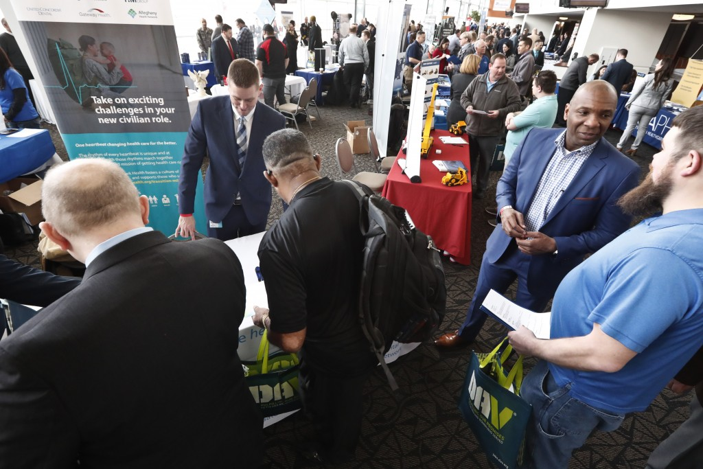 In this March 7, 2019, photo visitors to the Pittsburgh veterans job fair meet with recruiters at Heinz Field in Pittsburgh. Economists predict hiring...