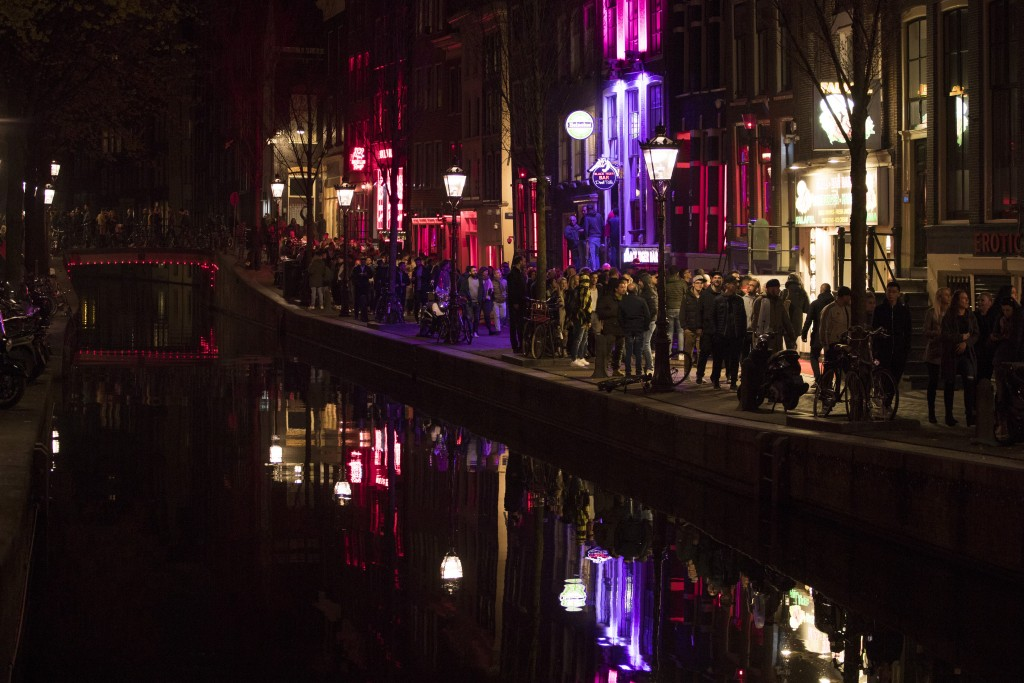 Tourists crowded the narrow canal-side streets in Amsterdam's red light district, Netherlands, Friday evening, March 29, 2019.  The Dutch capital plan