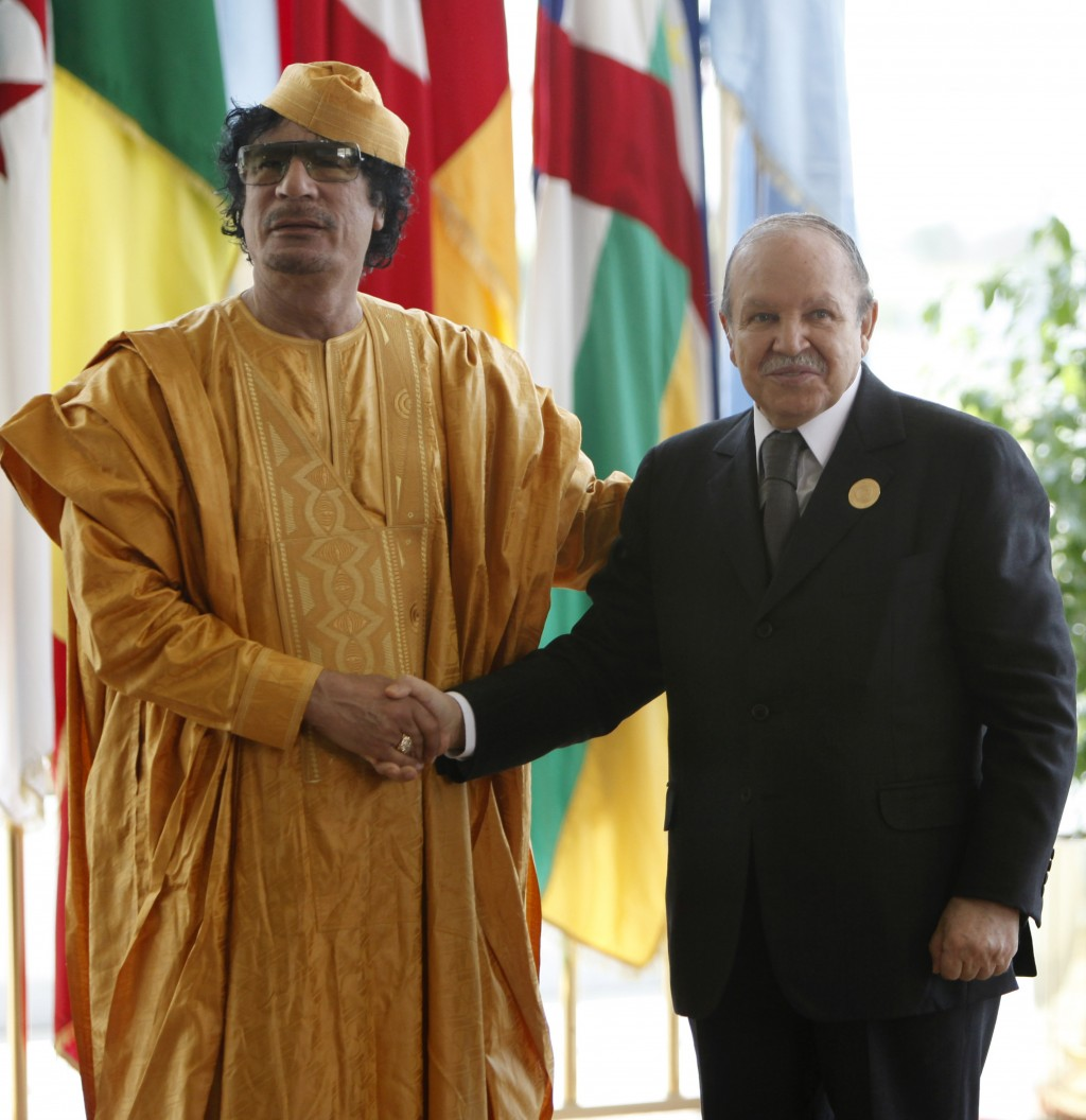 FILE - In this July 1, 2009 file photo, Libyan leader Moammar Gadhafi, left receives Algerian President Abdelaziz Bouteflika ahead of the opening sess...