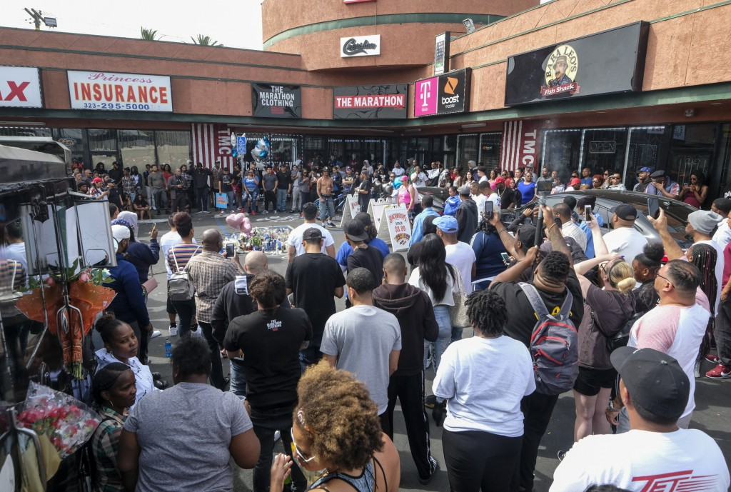 Fans of rapper Nipsey Hussle gather at a makeshift memorial in the parking lot of the Marathon Clothing store in Los Angeles, Monday, April 1, 2019. H