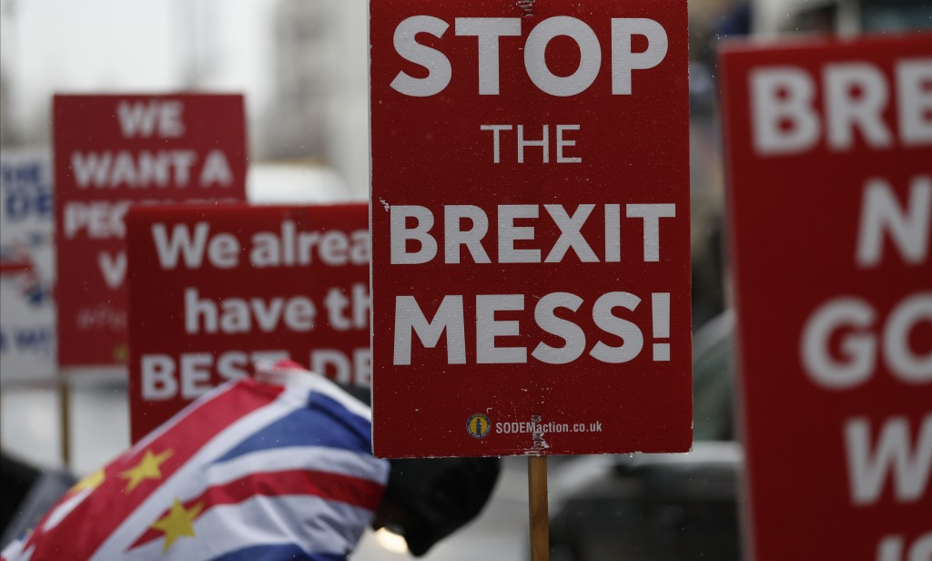 An anti Brexit protester and placards stand in the rain during demonstrations outside the Houses of Parliament in London, Tuesday, April 2, 2019. Brit