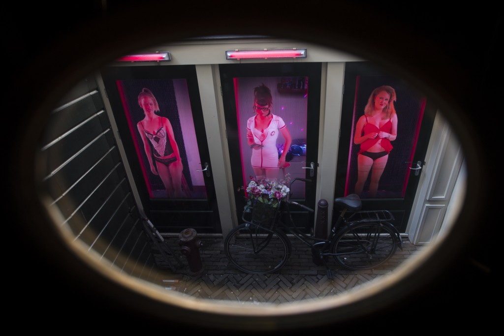 Three video's of women posing as sex workers are projected behind three doors at the Red Light Secrets Museum of Prostitution in Amsterdam's red light