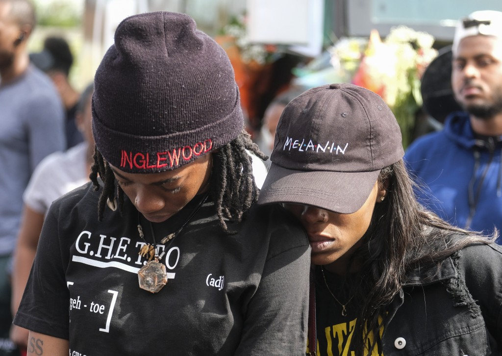 Fans of rapper Nipsey Hussle appear at a makeshift memorial in the parking lot of Hussle's Marathon Clothing store in Los Angeles, Monday, April 1, 20