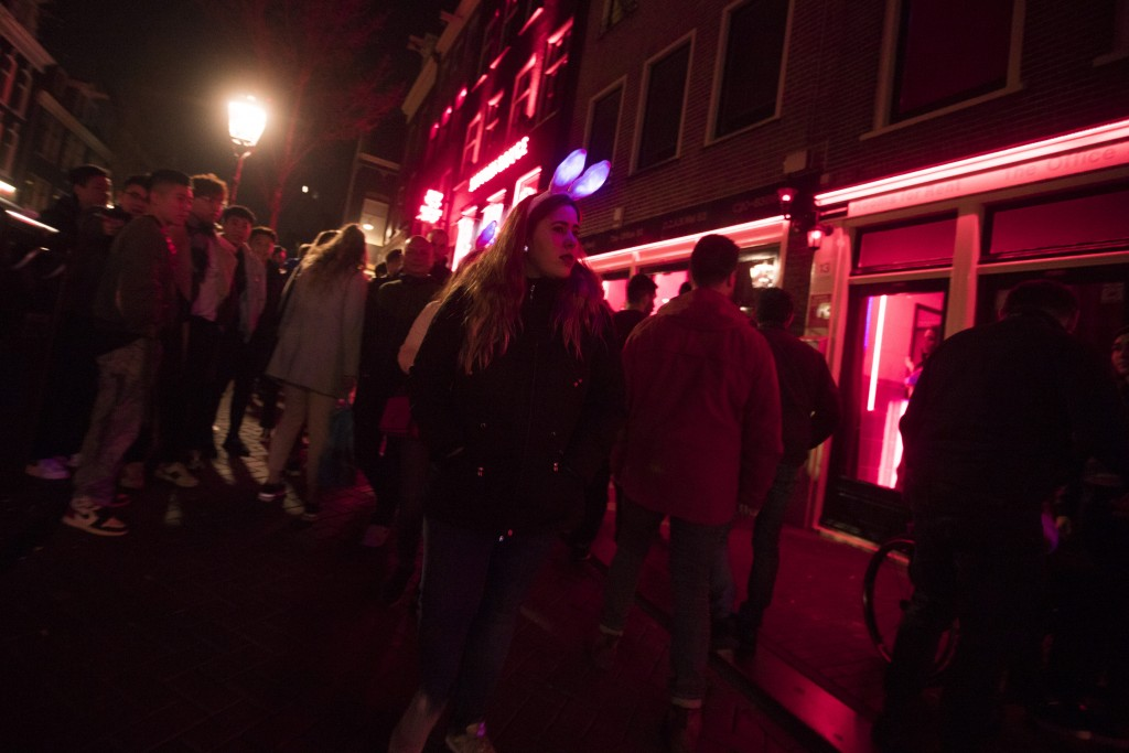 Tourists crowd the narrow canal-side streets in Amsterdam's red light district, Netherlands, Friday evening, March 29, 2019.  The Dutch capital has ba