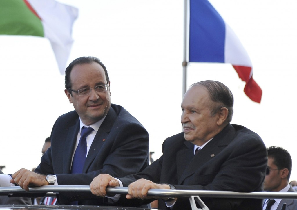 FILE  - In this Dec.19, 2012 file photo, French President Francois Hollande, left, and Algerian President Abdelaziz Bouteflika stand in a car as they ...