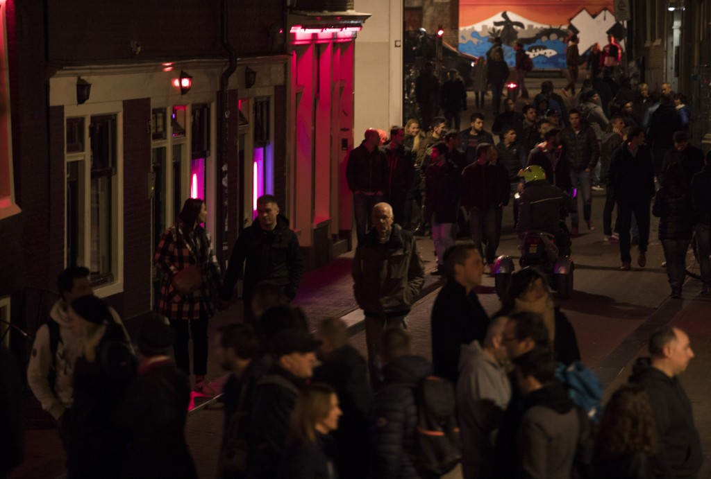 Tourists crowd the narrow canal-side streets in Amsterdam's red light district, Netherlands, Friday evening, March 29, 2019.  The Dutch capital plans