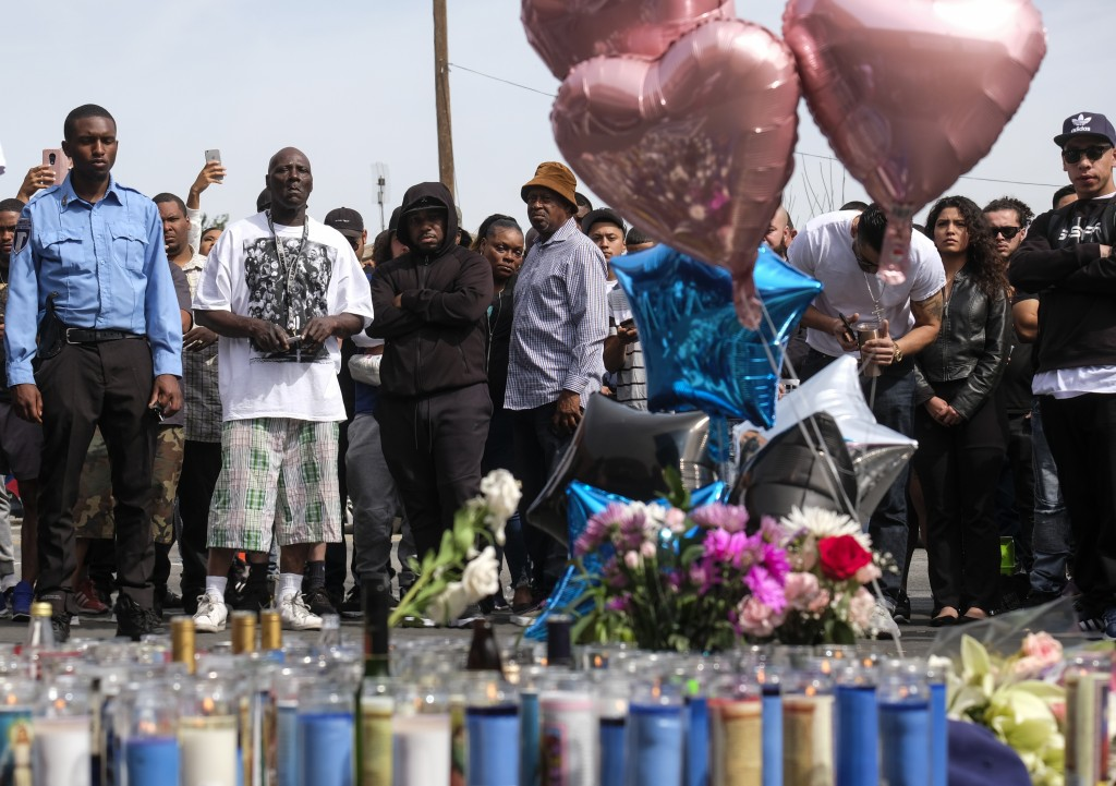 Fans of rapper Nipsey Hussle appear at a makeshift memorial in the parking lot of Hussle's Marathon Clothing store in Los Angeles, Monday, April 1, 20...
