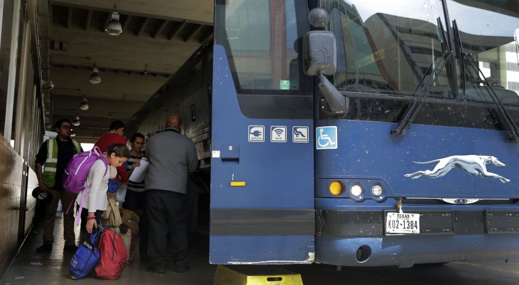 Immigrants from Central America seeking asylum board a bus, Tuesday, April 2, 2019, in downtown San Antonio. The surge of migrants arriving at the sou