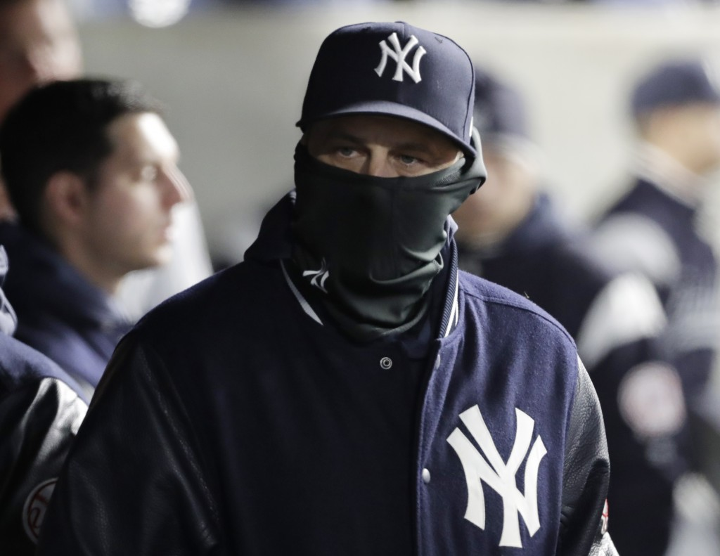 New York Yankees manager Aaron Boone wears a balaclava to keep warm during a baseball game against the Detroit Tigers, Tuesday, April 2, 2019, in New