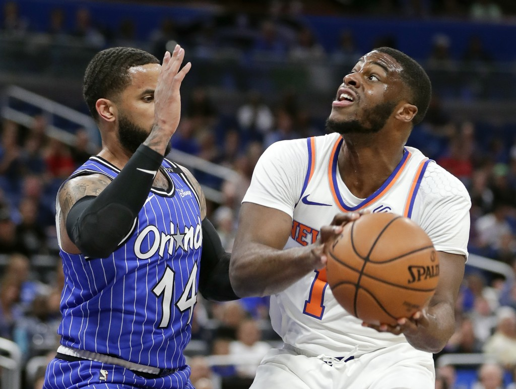 New York Knicks' Emmanuel Mudiay, right, looks for a shot against Orlando Magic's D.J. Augustin (14) during the first half of an NBA basketball game W...