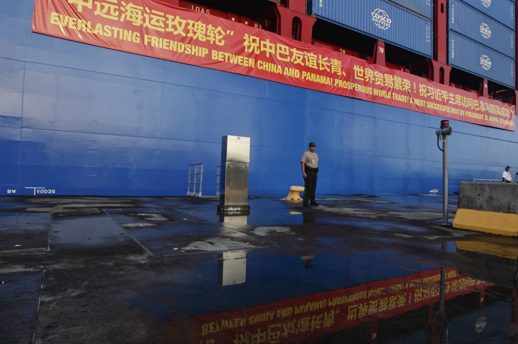 In this Dec. 3, 2018, photo, a Panama Canal guard stands at attention in front of a Chinese container ship docked at the Panama Canal's Cocoli Locks i...