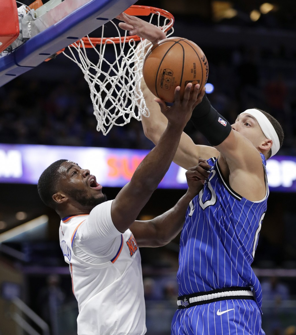 Orlando Magic's Aaron Gordon, right, blocks a shot by New York Knicks' Emmanuel Mudiay during the first half of an NBA basketball game Wednesday, Apri...