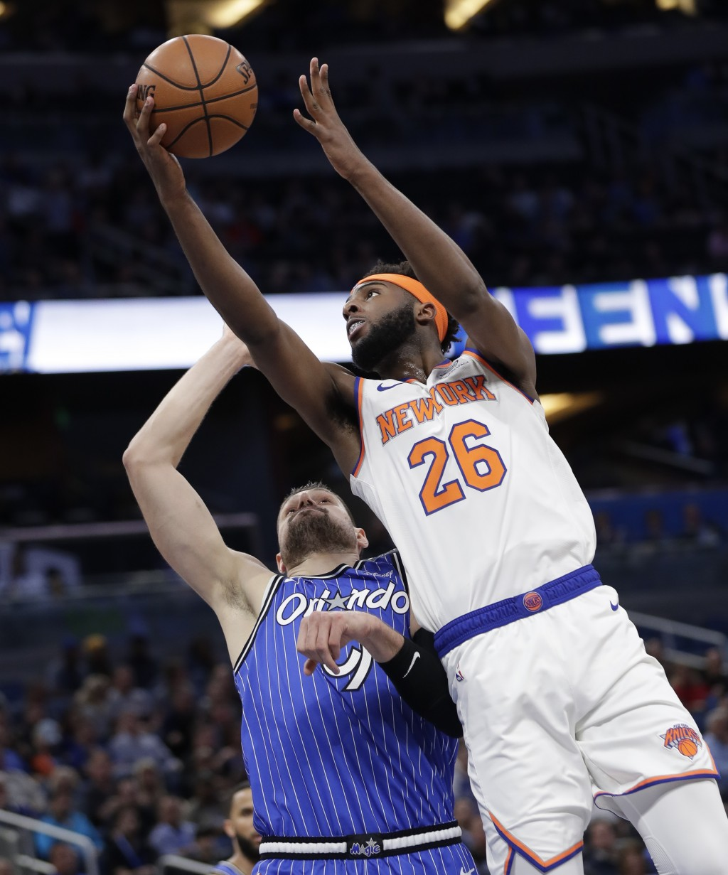 New York Knicks' Mitchell Robinson (26) makes a shot over Orlando Magic's Nikola Vucevic during the first half of an NBA basketball game Wednesday, Ap...
