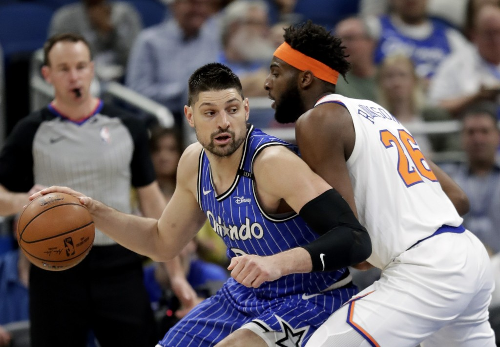 Orlando Magic's Nikola Vucevic, left, makes a move to get to the basket against New York Knicks' Mitchell Robinson during the first half of an NBA bas...