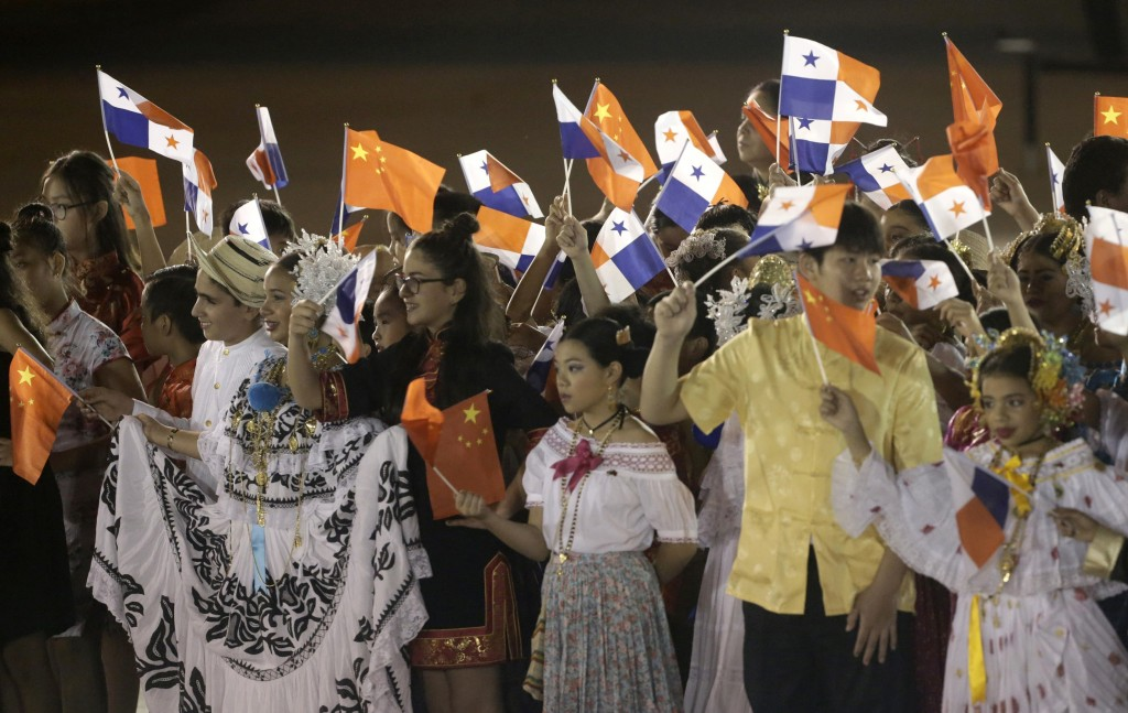 FILE - In this Dec. 2, 2018, file photo, children wave Panamanian and Chinese national flags during a welcome ceremony for China's President Xi Jinpin...