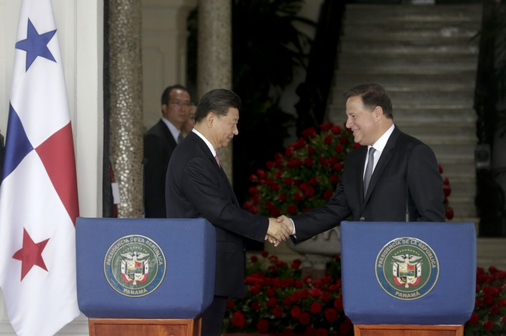 FILE - In this Dec. 3, 2018, file photo, Chinese President Xi Jinping, left, and Panama's President Juan Carlos Varela shakes hands after reading a st...