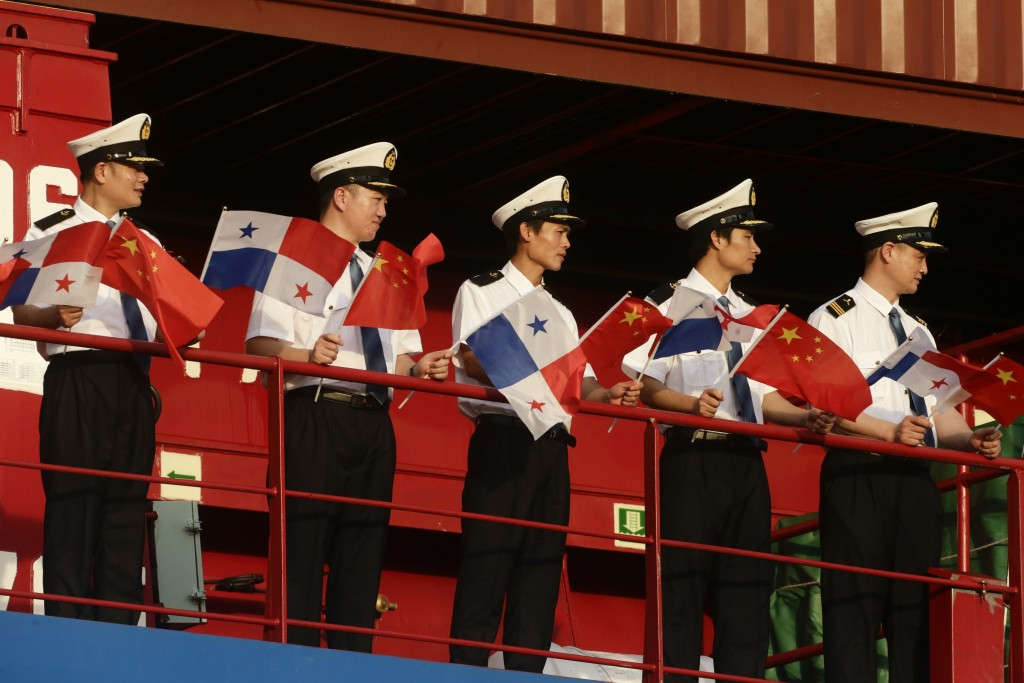 """FILE - In this Dec. 3, 2018, file photo, sailors on the Chinese flagged ship """"Cosco Shipping Rose"""" hold Panamanian and Chinese flags during a visit by..."""
