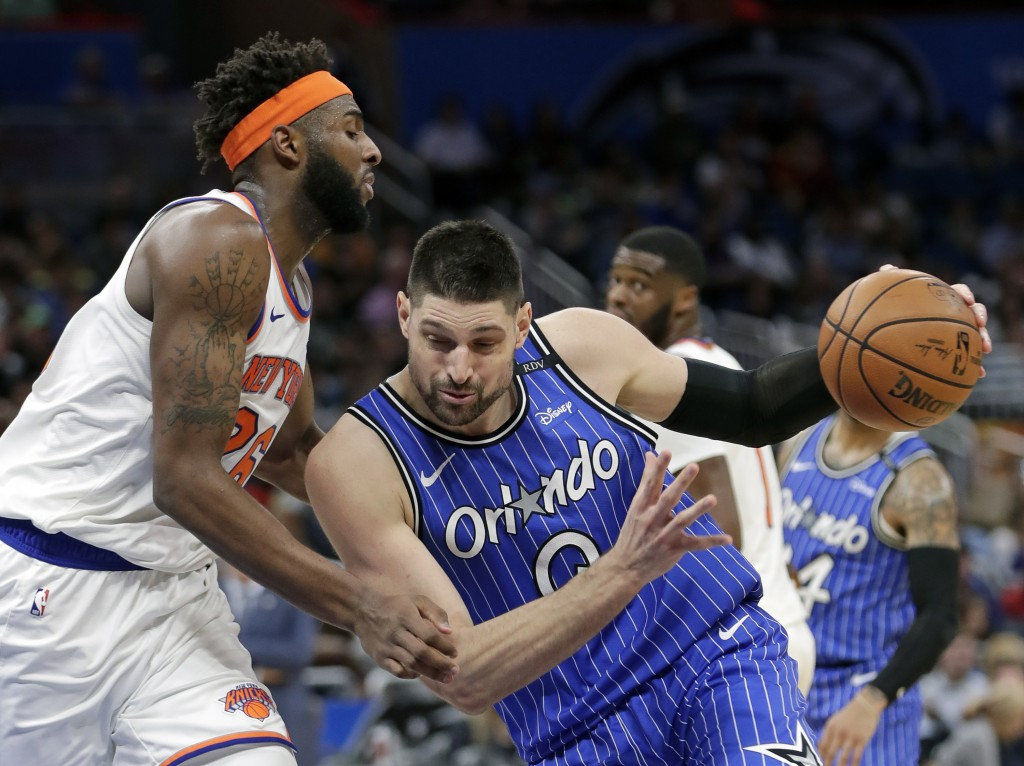 Orlando Magic's Nikola Vucevic, right, drives to the basket against New York Knicks' Mitchell Robinson during the second half of an NBA basketball gam...
