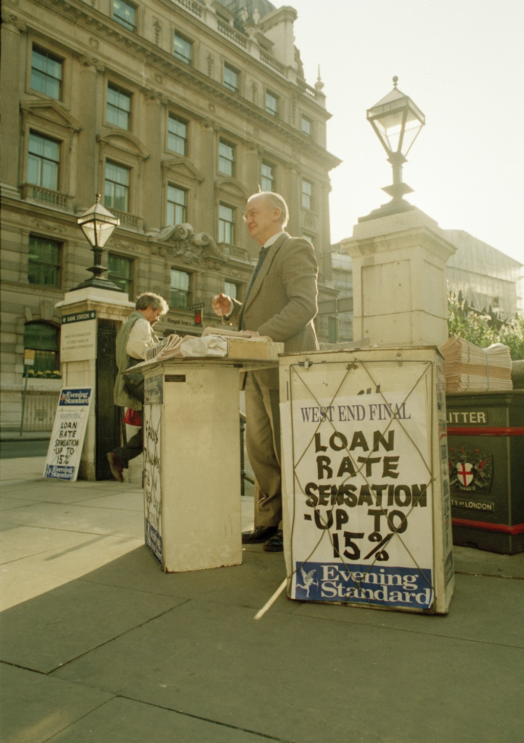 FILE - In this Sept. 16, 1992 file photo, a man sells newspapers outside the Bank of England as a sign reflects the financial news in London on the tu