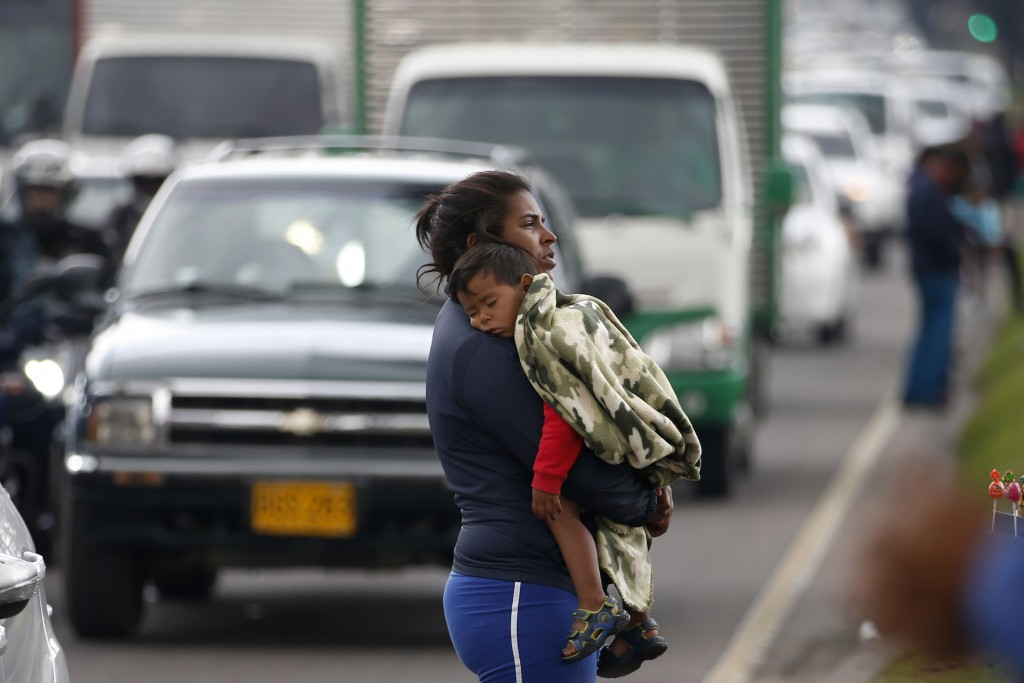 A Venezuelan migrant waits for traffic to come to a standstill so that she can ask drivers for spare change, in Bogota, Colombia, Thursday, April 4, 2...