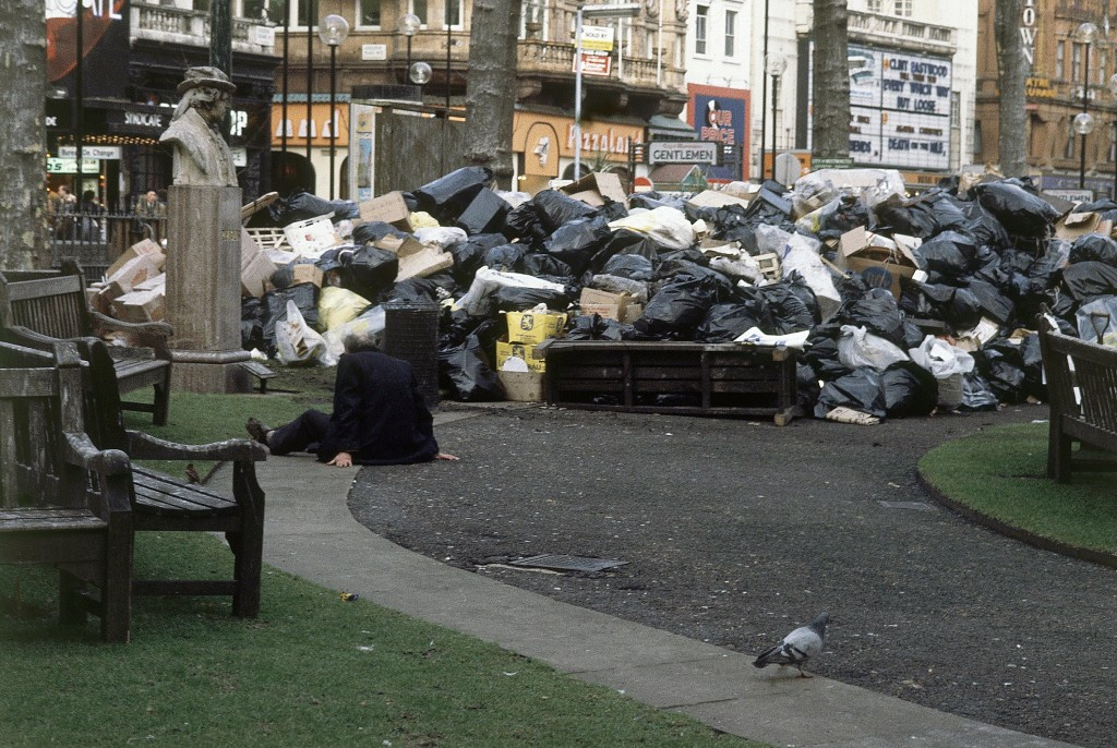 FILE - In this 1979 file photo, a man sits on the ground in front of a mound of garbage in London's Leicester Square, accumulated during a strike by c