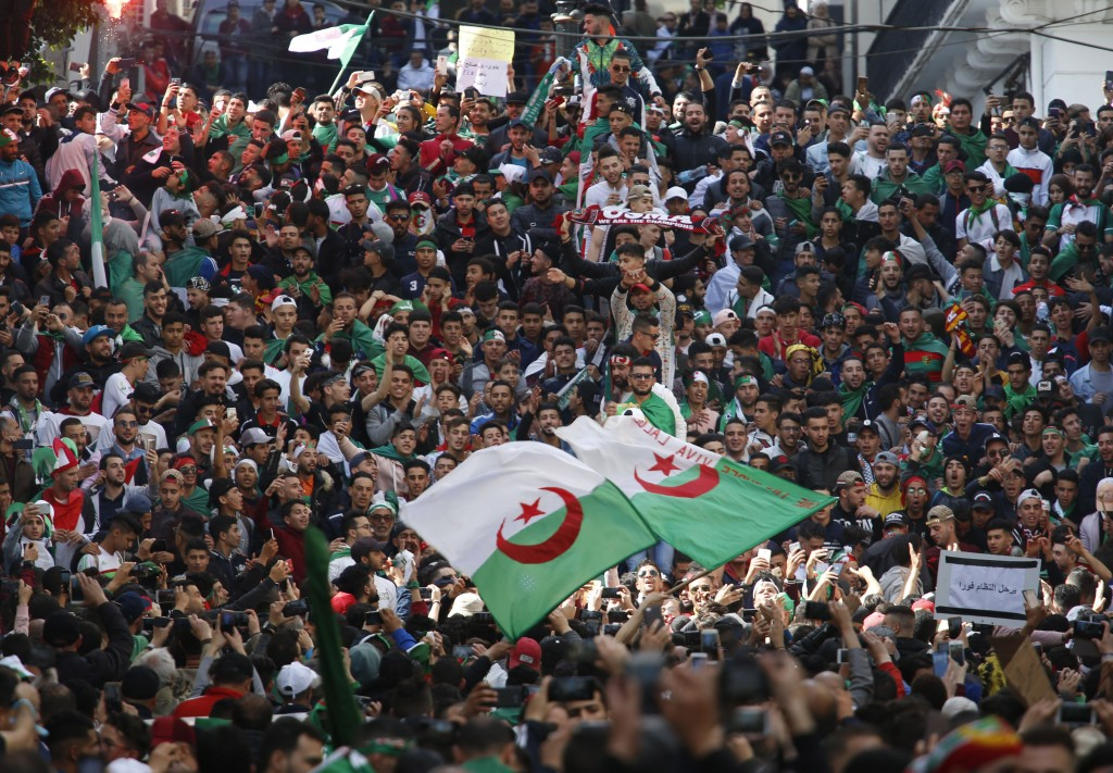 Demonstrators wave the Algerian flag as thousands gather for a rally in Algiers, Friday April 5, 2019, chanting, singing and cheering after their move...