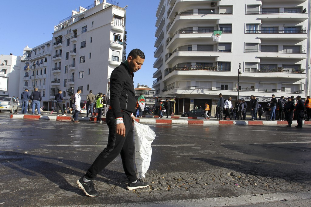 In this Friday March 29, 2019 image, groups of young people roam the streets picking up bottles and other detritus after Algeria's weekly pro-democrac...