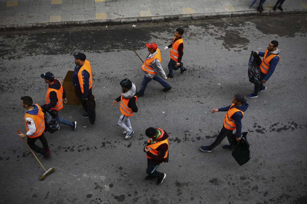 In this Friday March 22, 2019 image, groups of young people roam the streets picking up bottles and other detritus after Algeria's weekly pro-democrac...