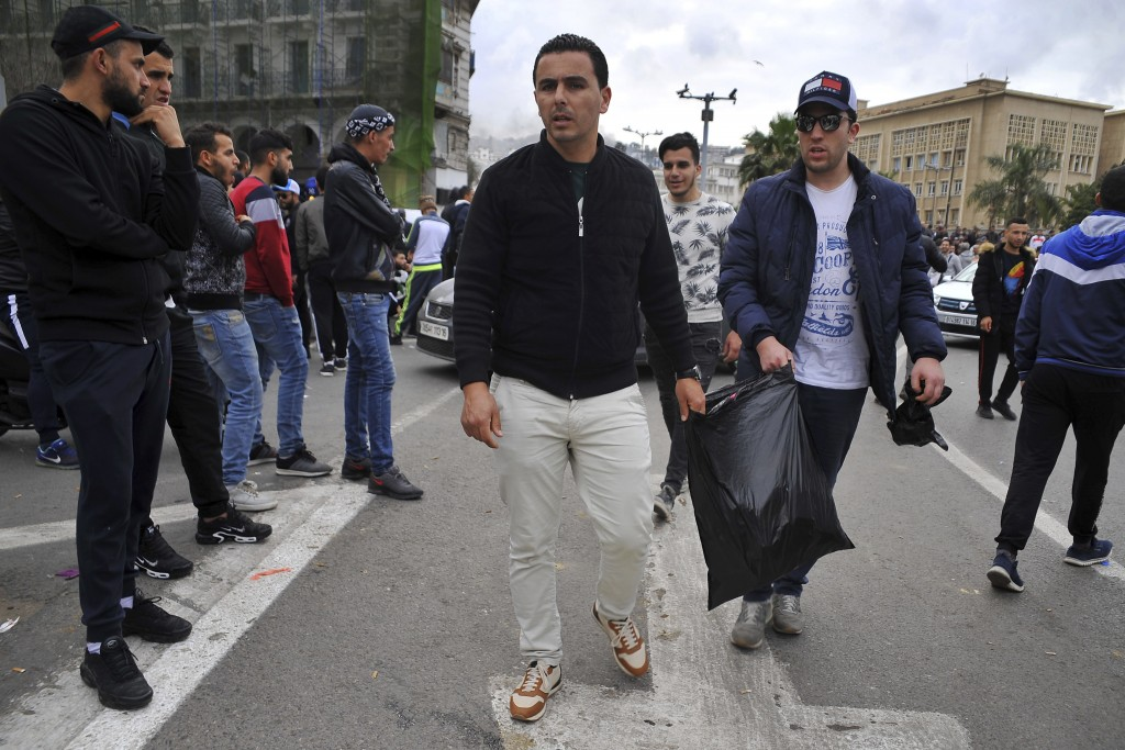 In this Friday March 8, 2019 image, groups of young people roam the streets picking up bottles and other detritus after Algeria's weekly pro-democracy...