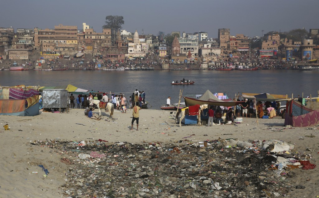 In this March 22, 2019, photo, trash is strewn on the banks of river Ganges, in Varanasi, India. Modi promised to clean up the Ganges, but gray water ...