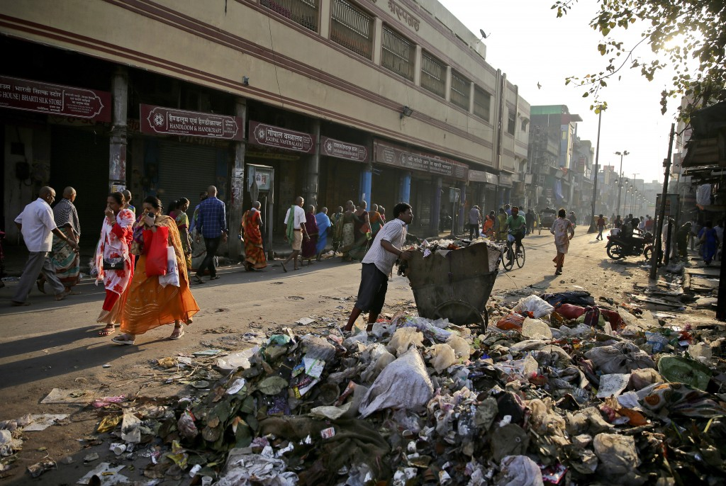In this March 22, 2019 photo, people cover their noses as they walk past trash strewn on a street, in Varanasi, India. A project in the ancient Indian...