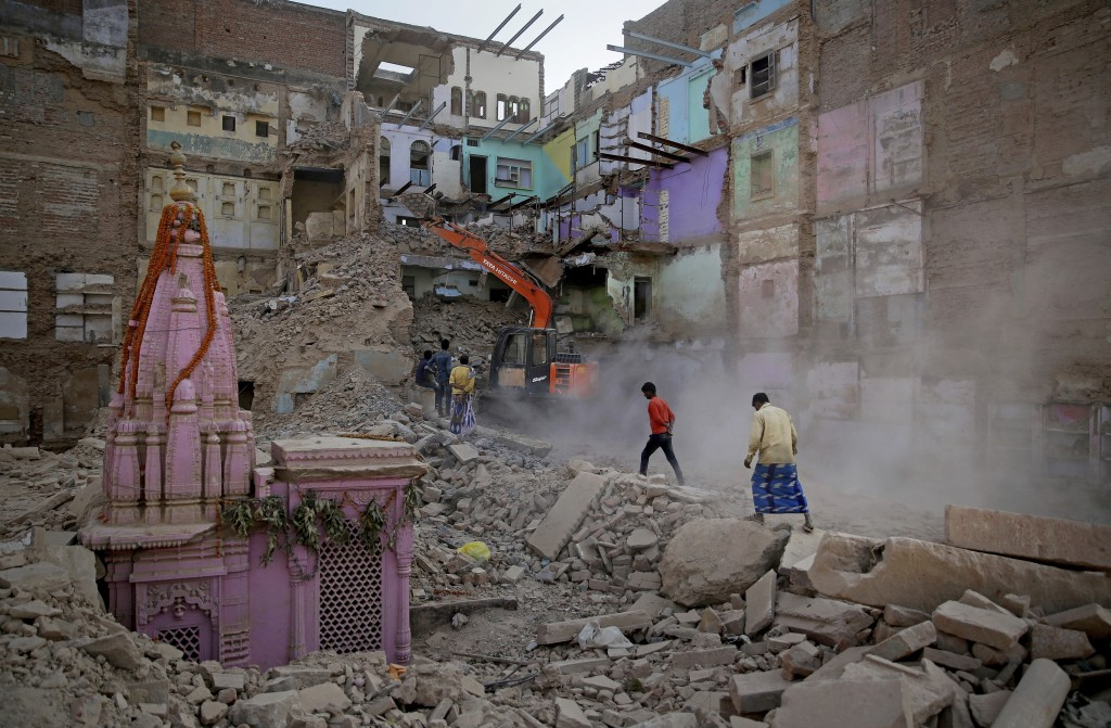 In this March 19, 2019, photo, locals walk past workers demolishing a house at the site of a proposed grand promenade connecting the sacred Ganges riv