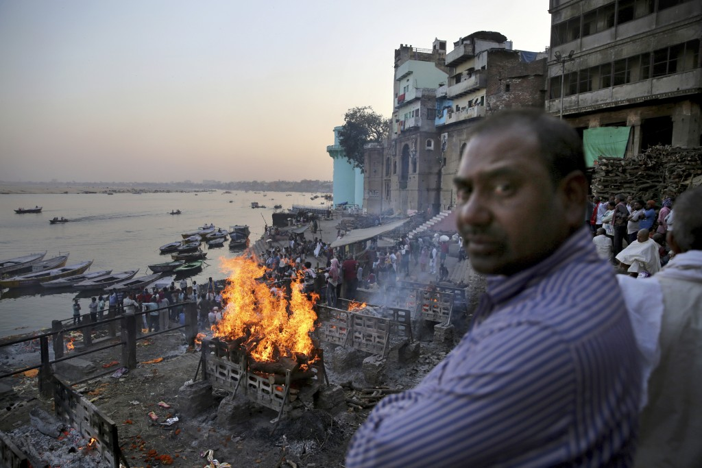 In this March 19, 2019, photo, funeral pyres burn on the banks of river Ganges, in Varanasi, India. According to ancient practice, funeral pyres burn ...