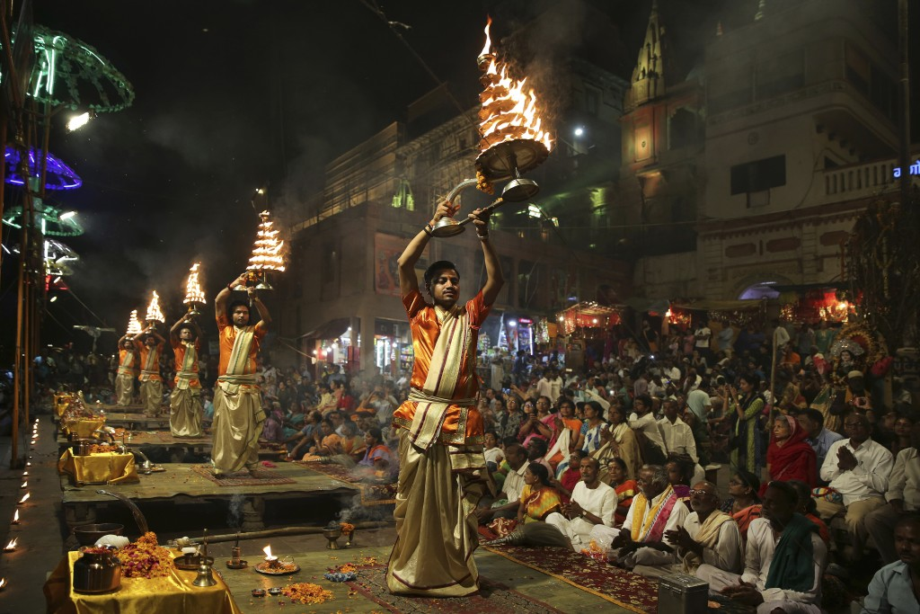 In this March 19, 2019, photo, devotees and tourists watch as Hindu priests perform daily rituals in reverence for river Ganges on its banks, in Varan...