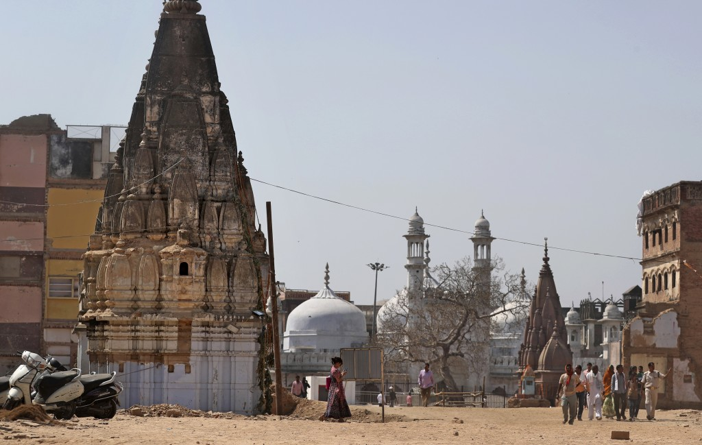 In this March 19, 2019, photo, 17th-century Gyanvapi mosque, white structure sandwiched between Hindu temples, is seen in the background as Hindu devo...