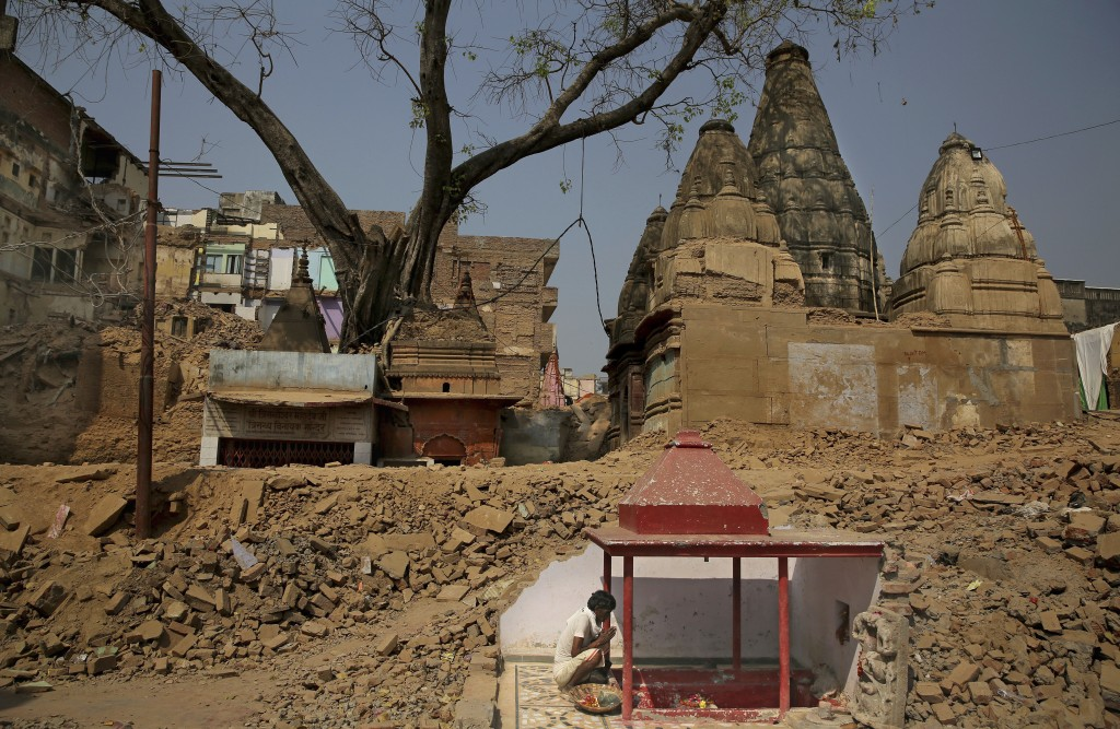 In this March 19, 2019 photo, a Hindu man prays next to a small temple uncovered hidden within the wall of demolished buildings at the site of a propo